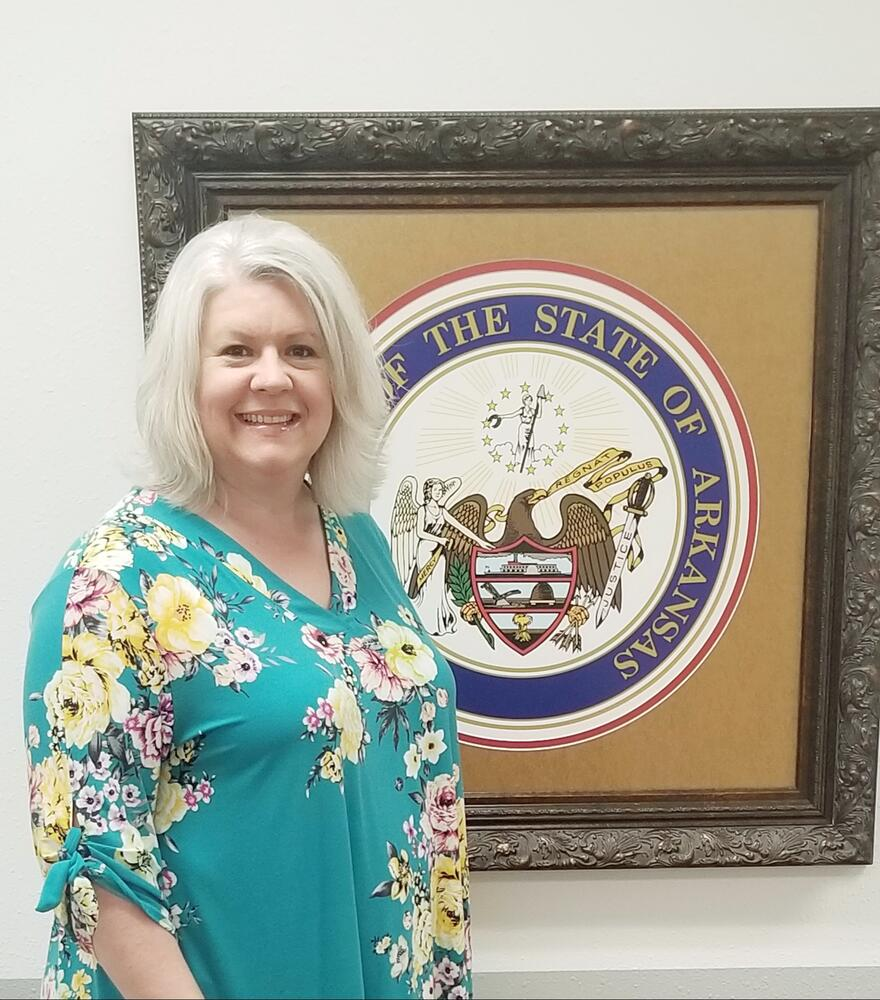 Crystal standing in front of Arkansas State Seal