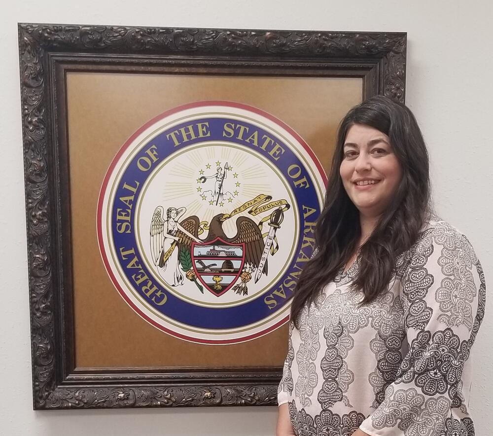 Beckie Standing in front of Arkansas State Seal