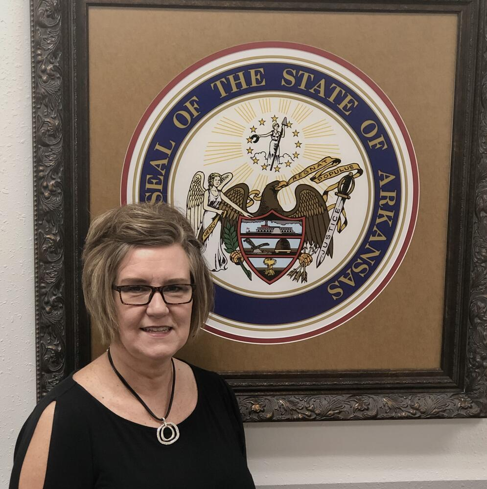 Tammy standing in front of Arkansas State Seal
