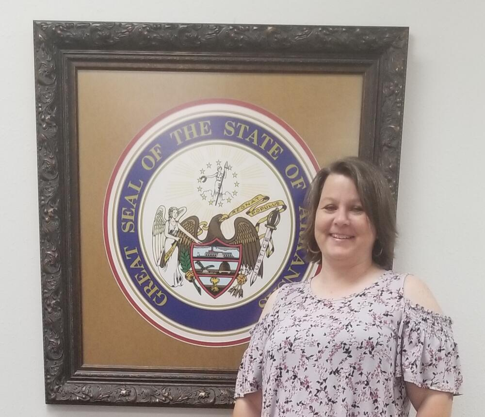Kristie standing in front of Arkansas State Seal